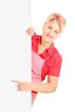 Blonde lächelnde Frau, die ein Schutzblech trägt und auf eine Platte gestikuliert Stockbild