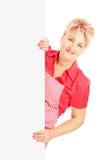 Blonde lächelnde Frau, die ein Schutzblech trägt und eine Platte hält Stockbild