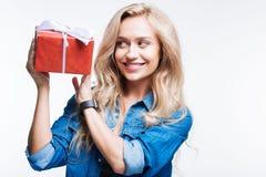 Blonde lächelnde Frau, die Geschenkbox hält Stockbilder