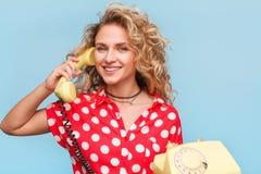 Blonde lächelnde Frau, die Hörer hält Lizenzfreies Stockfoto