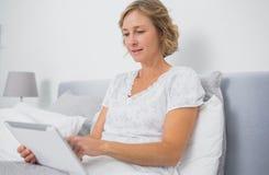 Blonde lächelnde Frau, die im Bett unter Verwendung des Tabletten-PC sitzt Stockfotos