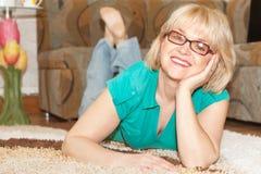 Blonde lächelnde Frau, die zu Hause auf Boden liegt Stockfotos