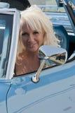 Blonde lächelnde Frau in einem Auto Stockfotos