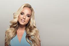Blonde lächelnde Frau mit dem gelockten schönen Haar Lizenzfreie Stockfotos