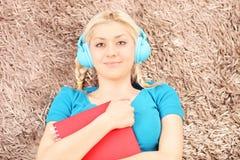 Blonde lächelnde Frau mit dem roten Notizbuch, das auf einem Teppich liegt Stockfoto