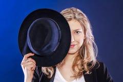 Blonde lächelnde Frau mit schwarzem Hut Lizenzfreie Stockfotos