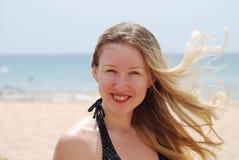 Blonde lächelnde Frauen mit Haarflugwesen Stockfotos