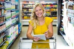 Blonde lächelnde Frauenprüfungsliste Lizenzfreie Stockbilder
