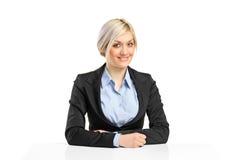 Blonde lächelnde Geschäftsfrau, die an ihrem Schreibtisch sitzt Stockbilder
