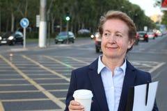 Blonde lächelnde Geschäftsfrau, die Wegwerfschale in der beschäftigten Stadtstraße mit Kopienraum hält Stockfotografie