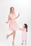 Blonde lächelnde Mutter und nette kleine Tochter in rosa Prinzessin Stockbild