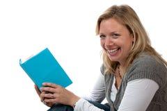 Blonde lächelnde, sitzende und lesende Frau Stockbild