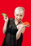 Blonde lächelnde und haltene Gurke und Tomate Stockbild
