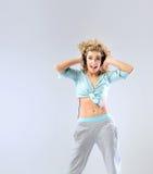 Blonde lachende Frau, die Musik hört Stockbilder