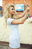 Blonde lady with beautiful smile. Young fashionable beautiful blonde woman posing outdoor in casual clothes. Girl with long curly hair stock images