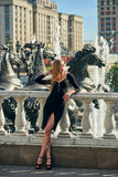 Blonde lady in black dress with decolletage. Beautiful blonde lady in black dress with decolletage at Park and Horses fountain in Alexander Garden at the Royalty Free Stock Photo