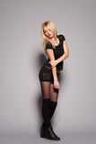 Blonde lady in black posing on grey background Stock Photography