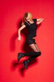 Blonde lady in black posing on red Royalty Free Stock Photo