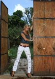 Blonde lady leaning against stable doors Royalty Free Stock Photography
