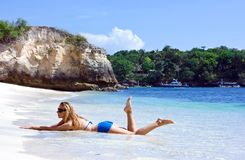 Blonde lady lying in water on the beach Royalty Free Stock Image