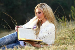 Blonde lady reading Bible. A beautiful young blonde lady in her twenties is reading her Bible outside ina park Stock Images