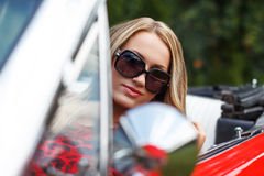 Blonde lady in red cabriolet Stock Photos