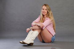 Blonde lady with shirts and white boots Royalty Free Stock Photography