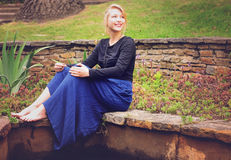 Blonde lady sitting next to a pnd in a park Royalty Free Stock Images
