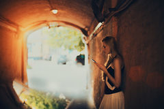 Blonde lady with smartphone in tunnel Stock Images