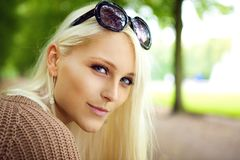 Blonde Lady With Sunglasses. Close up of the face of a sexy blonde lady with sunglasses balanced on top of her forehead in a park Stock Images