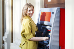 Blonde lady using an automated teller machine. Woman withdrawing money or checking account balance Stock Image