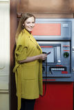 Blonde lady using an automated teller machine Royalty Free Stock Images