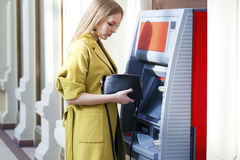 Blonde lady using an automated teller machine Royalty Free Stock Photo