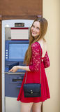 Blonde lady using an automated teller machine Stock Photography