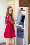 Blonde lady using an automated teller machine Stock Image