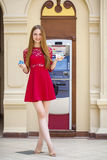 Blonde lady using an automated teller machine Stock Images