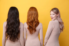 Blonde lady winking to camera near brunette and redhead women. Stock Photography