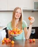Blonde langhaarige Frau, die Aprikosen in der Hauptküche isst Stockfoto