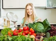 Blonde langhaarige Frau, die mit Gemüse kocht Stockbild
