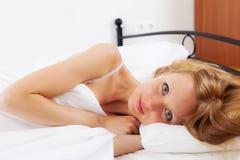 Blonde langhaarige Frau, die oben aufwacht   im Bett Lizenzfreie Stockbilder