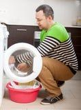 Blonde langhaarige Frau, die zu Hause Waschmaschine verwendet Lizenzfreie Stockbilder