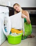 Blonde langhaarige Frau, die zu Hause Waschmaschine verwendet Lizenzfreie Stockfotos