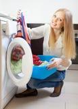 Blonde langhaarige Frau, die zu Hause Waschmaschine verwendet Stockbild