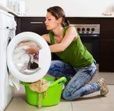 Blonde langhaarige Frau, die zu Hause Waschmaschine verwendet Stockbilder