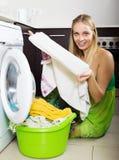 Blonde langhaarige Frau, die zu Hause Waschmaschine verwendet Stockfotografie