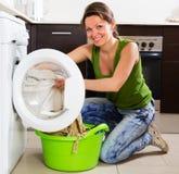 Blonde langhaarige Frau, die zu Hause Waschmaschine verwendet Lizenzfreie Stockfotografie