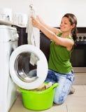 Blonde langhaarige Frau, die zu Hause Waschmaschine verwendet Lizenzfreies Stockbild