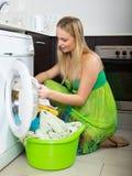 Blonde langhaarige Frau, die zu Hause Waschmaschine verwendet Stockfotos