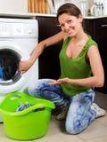 Blonde langhaarige Frau, die zu Hause Waschmaschine verwendet Stockfoto