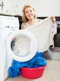 Blonde langhaarige Frau, die zu Hause Waschmaschine verwendet Frau, die zu Hause Waschmaschine verwendet Stockbild